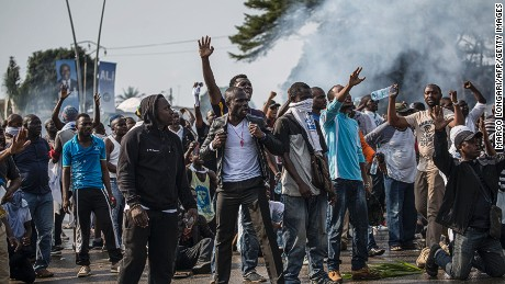 "TOPSHOT - Supporters of Gabonese opposition leader Jean Ping face security forces (unseen) blocking the demonstration trying to reach the electoral commission in Libreville on August 31, 2016, as part of a protest sparked after Gabon's president Ali Bongo was declared winner of last weekend's contested election.  Protesters shouting ""Ali must go!"" tried to storm the offices of the election commission shortly after authorities announced his re-election by a narrow majority. Bongo won by a narrow 5,594 votes of a total 627,805 registered voters. Turnout was 59.46 percent nationwide but soared to 99.93 percent in one of the country's nine provinces -- the Haut-Ogooue, heartland of Bongo's Teke ethnic group -- in a result hotly contested by the opposition. / AFP / MARCO LONGARI        (Photo credit should read MARCO LONGARI/AFP/Getty Images)"