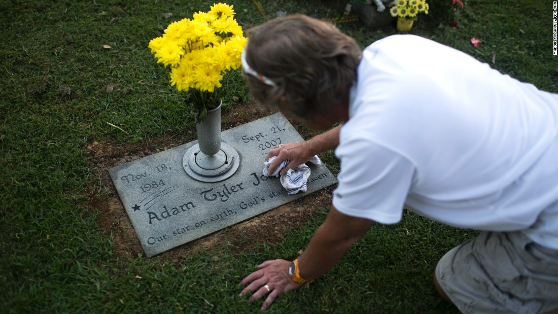 Teddy Johnson polishes the grave of his son, Adam, who died of a heroin overdose in 2007.