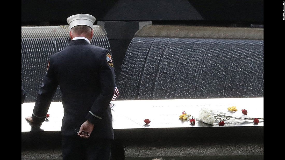 """A firefighter touches the names of those who died in the 9/11 attacks at a memorial in New York on Sunday, September 11. <a href=""""http://www.cnn.com/2016/09/08/us/new-york-9-11-magnum-photographers/index.html"""" target=""""_blank"""">9/11 images are seared into the memories of Magnum photographers</a>"""