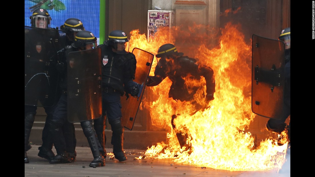"""A riot police officer is surrounded by flames during a demonstration against new labor law reforms in Paris on Thursday, September 15. <a href=""""http://www.cnn.com/2016/06/02/europe/france-strikes-labor-reform-bill/index.html"""" target=""""_blank"""">Demonstrations against the reforms</a> -- which include changes in the number of hours staff are expected to work and easier means for companies to hire and fire people -- have been taking place for about six months throughout France."""