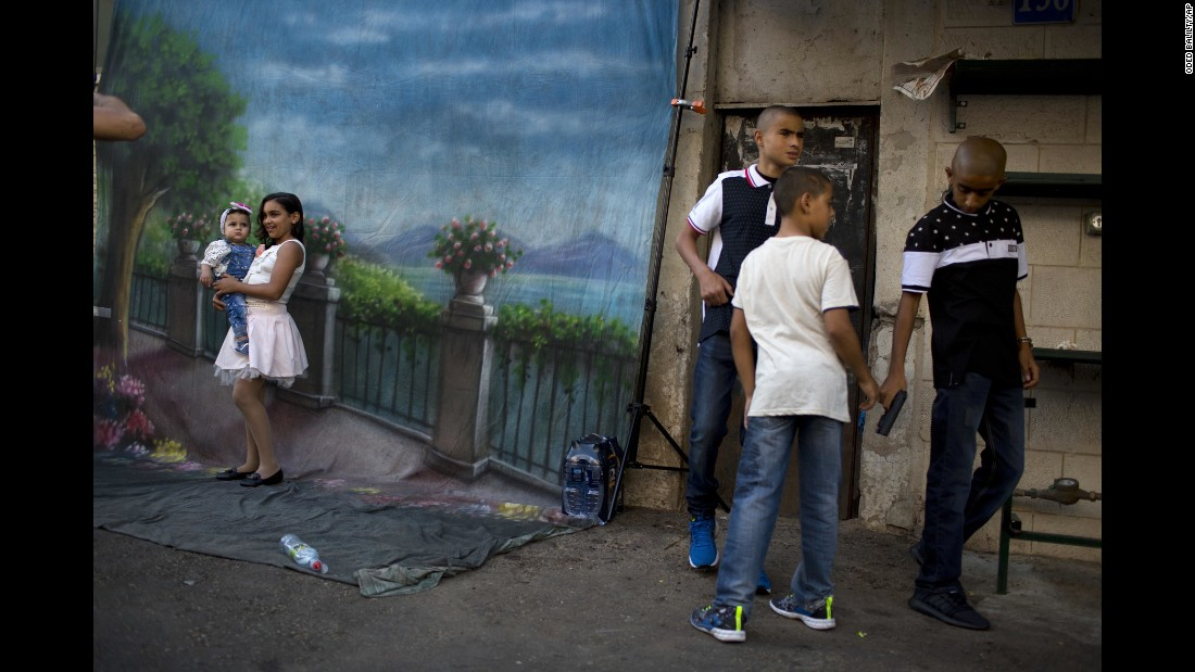 Girls pose for a photo while three boys play with a toy gun during Eid al-Adha in Jaffa, Israel, on Monday, September 12.