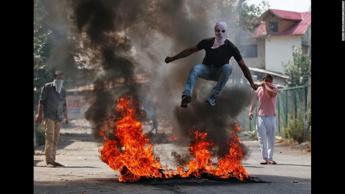 A man jumps over burning debris -- during a protest against recent Kashmir killings -- in Srinagar, India, on Monday, September 12.