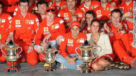 Felipe Massa poses with wife Anna Rafaela and Ferrari staff after winning the 2008 GP in Bahrain.