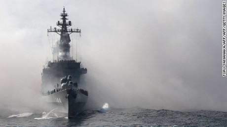 Japan's Maritime Self-Defense Force (MSDF) escort ship Kurama sails through smoke during a fleet review off Sagami Bay, Kanagawa prefecture, on October 18, 2015.