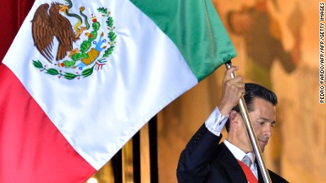 """Mexican President Enrique Pena Nieto waves the Mexican National Flag on the main balcony of the National Palace during ceremonies called """"The Shout"""" marking the start of celebrations of Independence Day in Mexico City on September 15, 2016. / AFP / Pedro Pardo        (Photo credit should read PEDRO PARDO/AFP/Getty Images)"""