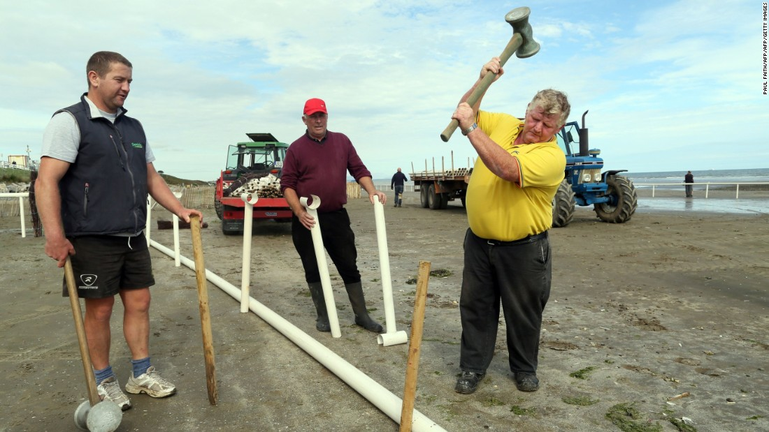 Men work to erect the temporary race course on Laytown beach.