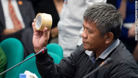Edgar Matobato holds roll of a packing tape as he testifies during a senate hearing in Manila on September 15, 2016. He said it was used to mask victims' identities.