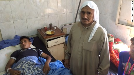 Mahmud Jassim, 16, receives treatment at Aleppo. His  father is by his side.