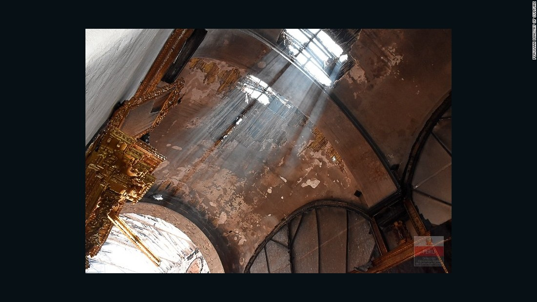 Light beams shine through ceiling damage to the historic Cusco church.