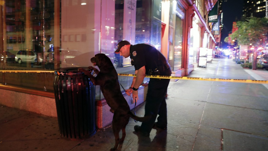 A New York police officer and his dog check a garbage can close to the scene of the explosion.