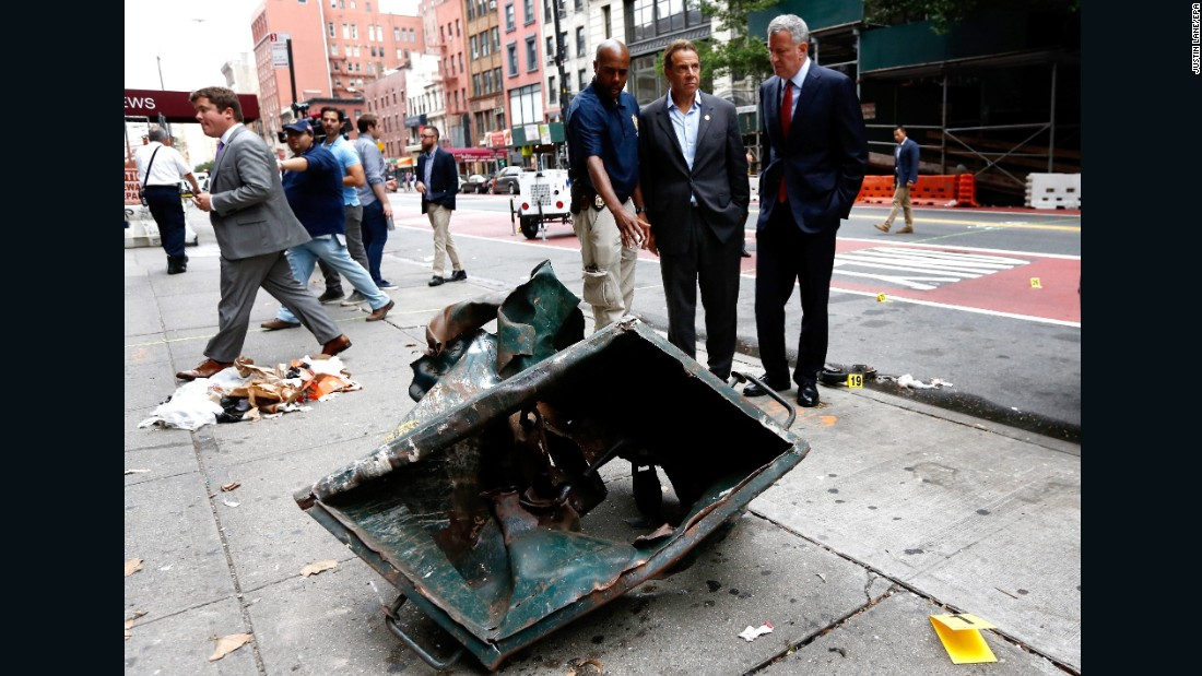 New York Mayor Bill de Blasio, right, and New York Gov. Andrew Cuomo, second right, look over the mangled remains of a dumpster Sunday, September 18, in New York's Chelsea neighborhood. An explosion injured 29 people there the night before.