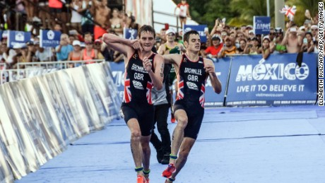 TOPSHOT - British athlete Alistair Brownlee (L) helps his brother Jonathan Brownlee (R) before crossing the line in second and third place during the ITU World Triathlon Championships 2016 in Cozumel, Quintana Roo, Mexico on September 18, 2016. / AFP / ELIZABETH RUIZ        (Photo credit should read ELIZABETH RUIZ/AFP/Getty Images)