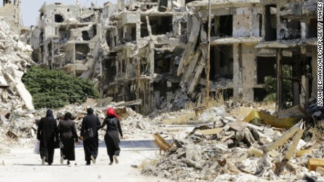 Syrian women walk in between destroyed buildings in the government-held Jouret al-Shiah neighbourhood of the central Syrian city of Homs on September 19, 2016. / AFP / LOUAI BESHARA        (Photo credit should read LOUAI BESHARA/AFP/Getty Images)