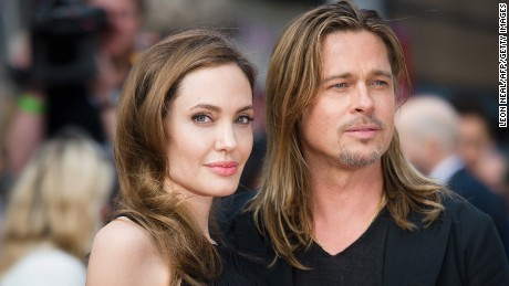 """Actress and humanitarian campaigner Angelina Jolie poses with her actor and fiance Brad Pitt as she arrives for the UK premiere of Brad Pitt's latest film """"World War Z"""" in Leicester Square in central London in 2013. Jolie,"""