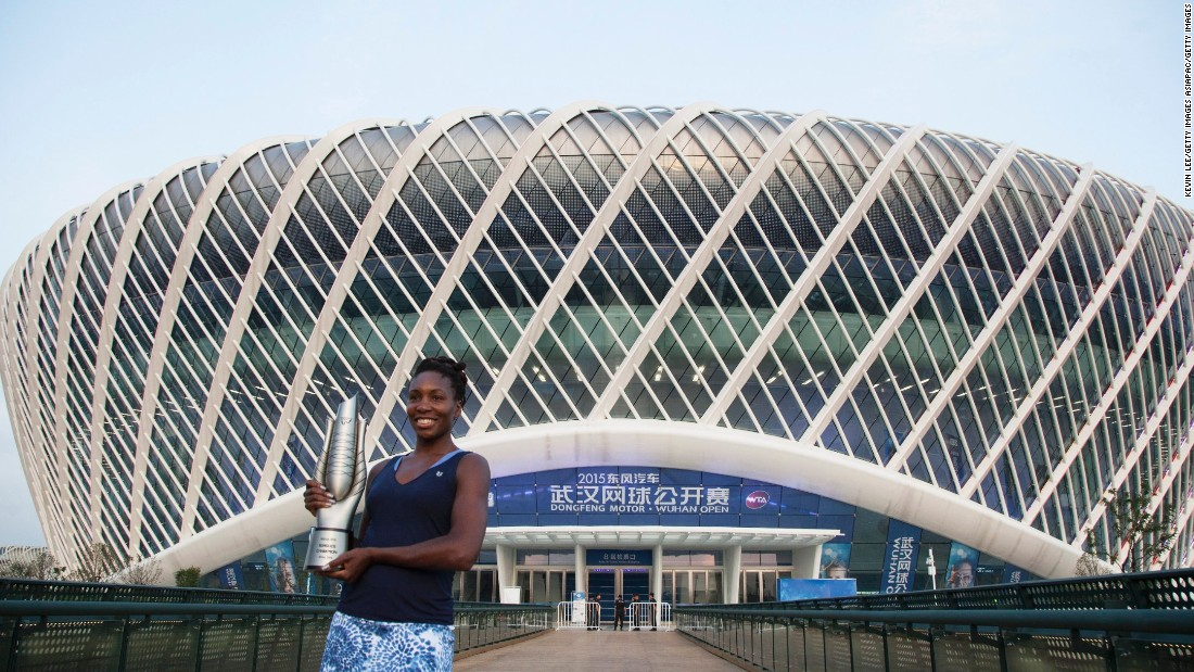 Venus Williams posing with the Wuhan Open trophy, the 47th singles title of her career,  in front of the stadium after she beat Spain's Garbine Muguruza in last year's final.