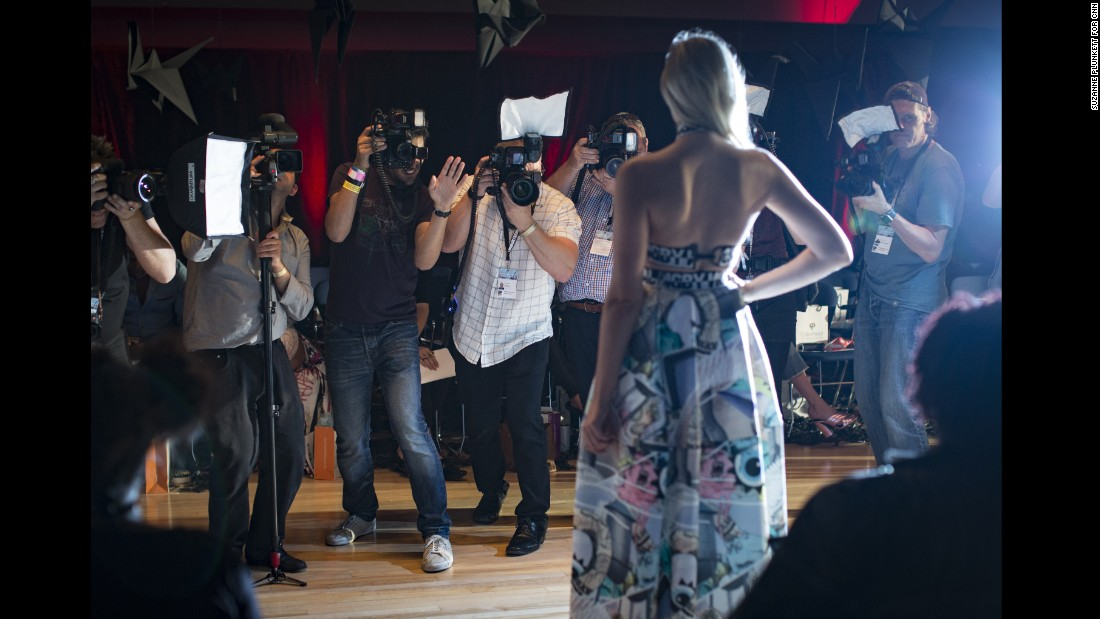 "Celebrity photographers shoot arrivals of front row guests before the Vin & Omi catwalk show on September 19. ""I once saw a fantastic fight in Milan,"" Moore recalls. ""Some French guy had nicked some Italian guy's spot. Everyone was on their boxes and they started to have a proper tear-up. One of them hit the other one and literally half the photographers went down like a house of cards."""
