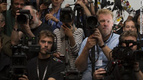 Photographer Jonas Gustavsson (R) poses for a portrait while he waits for the start of the Mary Katrantzou catwalk show during London Fashion Week, September 18, 2016.