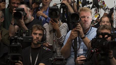 Jonas Gustavsson (R) waits for the start of the Mary Katrantzou catwalk show.