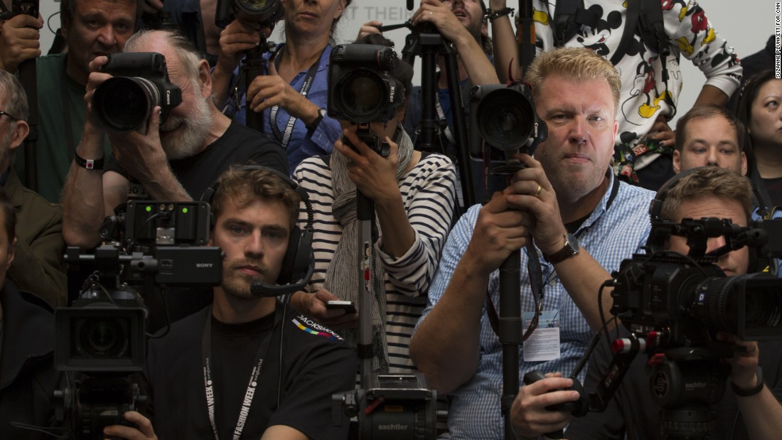 Photographer Jonas Gustavsson (R) poses for a portrait while he waits for the start of the Mary Katrantzou catwalk show on September 18.