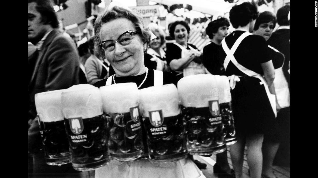 """A waitress carries several glasses of beer in 1979. Munich <a href=""""http://www.cnn.com/2010/WORLD/europe/09/21/germany.oktoberfest/"""" target=""""_blank"""">prides itself on its quality of beer,</a> unashamedly calling it the best in the world. It cites Bavarian Purity Requirements that allow only water, hops and barley to be used in the brewing process."""