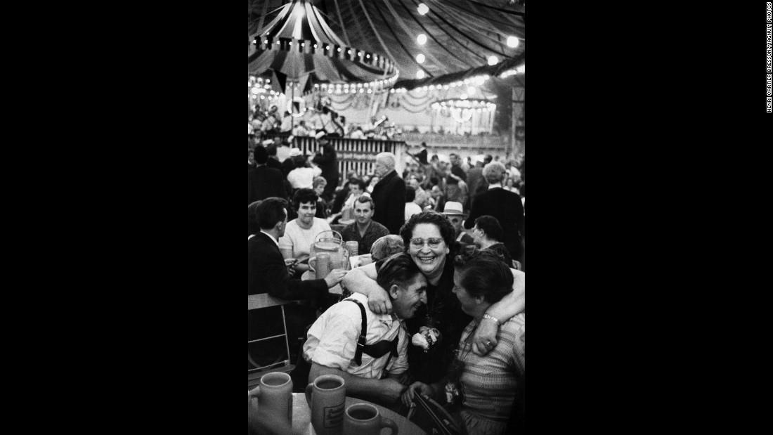 A woman hugs two people at Oktoberfest in 1961.
