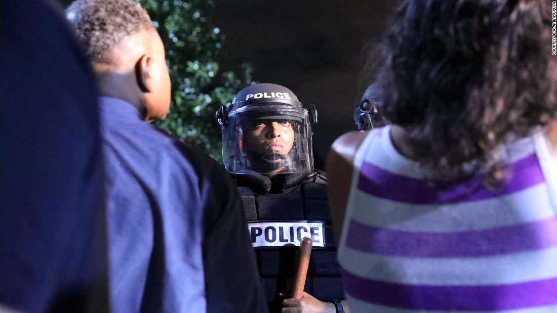 A police officer faces protesters.