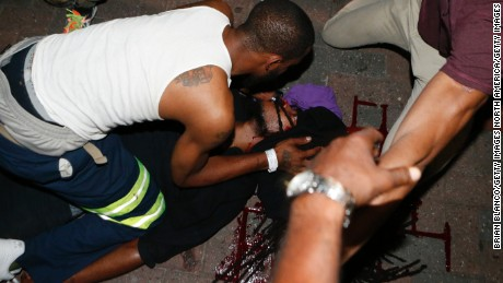CHARLOTTE, NC - SEPTEMBER 21:  Protesters tend to a seriously wounded protester in the parking area of the the Omni Hotel during a march to protest the death of Keith Scott September 21, 2016 in Charlotte, North Carolina. Scott, who was black, was shot and killed at an apartment complex near UNC Charlotte by police officers, who say they warned Scott to drop a gun he was allegedly holding.  (Photo by Brian Blanco/Getty Images)