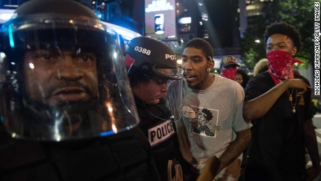 Protesters taunt riot police during a demonstration against police brutality in Charlotte, North Carolina, on September 21, 2016, following the shooting of Keith Lamont Scott the previous day.A protester in Charlotte, North Carolina was fatally shot by a civilian during a second night of unrest after the police killed a black man, officials said. / AFP / NICHOLAS KAMM        (Photo credit should read NICHOLAS KAMM/AFP/Getty Images)