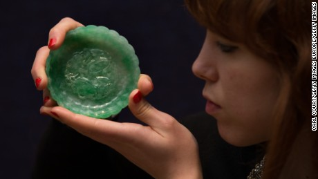 "LONDON, ENGLAND - MAY 10:  A member of staff holds an ""exceptional apple-green jadeite 'chrysanthemum' washer"" at Bonhams auction house on May 10, 2016 in London, England. Forming part of the Fine Chinese Art sale on the 12th May the set is expected to fetch between 20,000-30,000GBP. (Photo by Carl Court/Getty Images)"