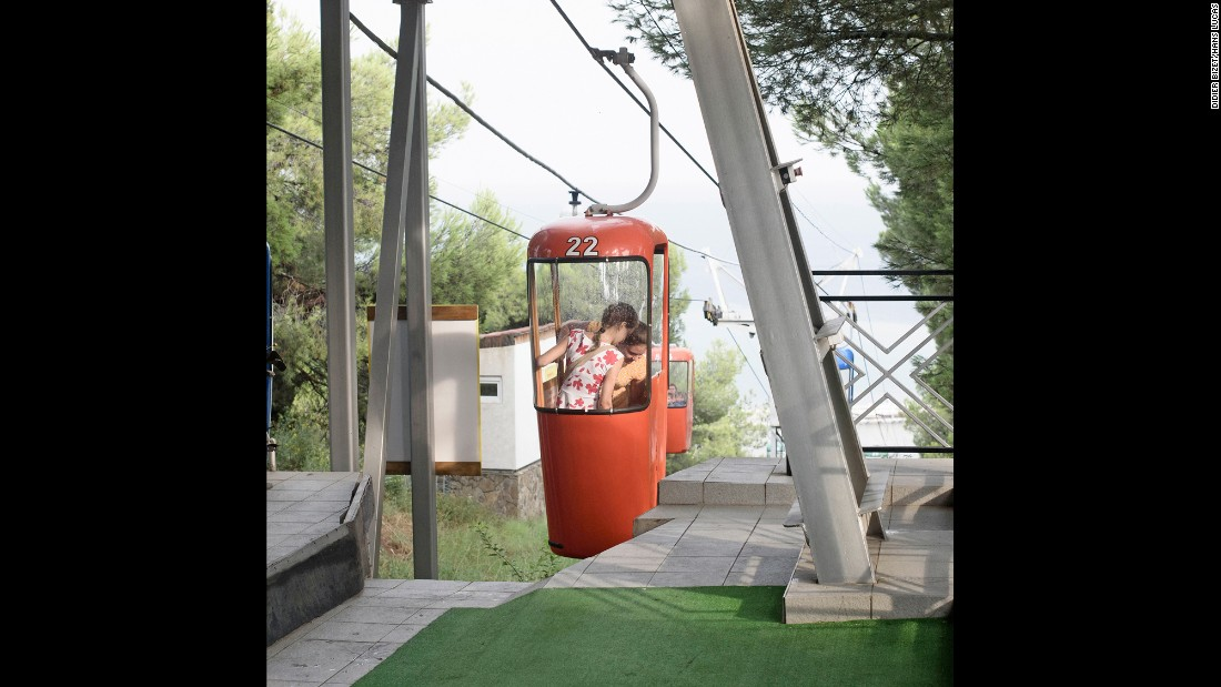 A child rides on a cable car.