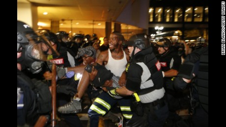 CHARLOTTE, NC - SEPTEMBER 21:  Police and protesters carry a seriously wounded protester into the parking area of the the Omni Hotel during a march to protest the death of Keith Scott September 21, 2016 in Carolina. Scott, who was black, was shot and killed at an apartment complex near UNC Charlotte by police officers, who say they warned Scott to drop a gun he was allegedly holding.  (Photo by Brian Blanco/Getty Images)