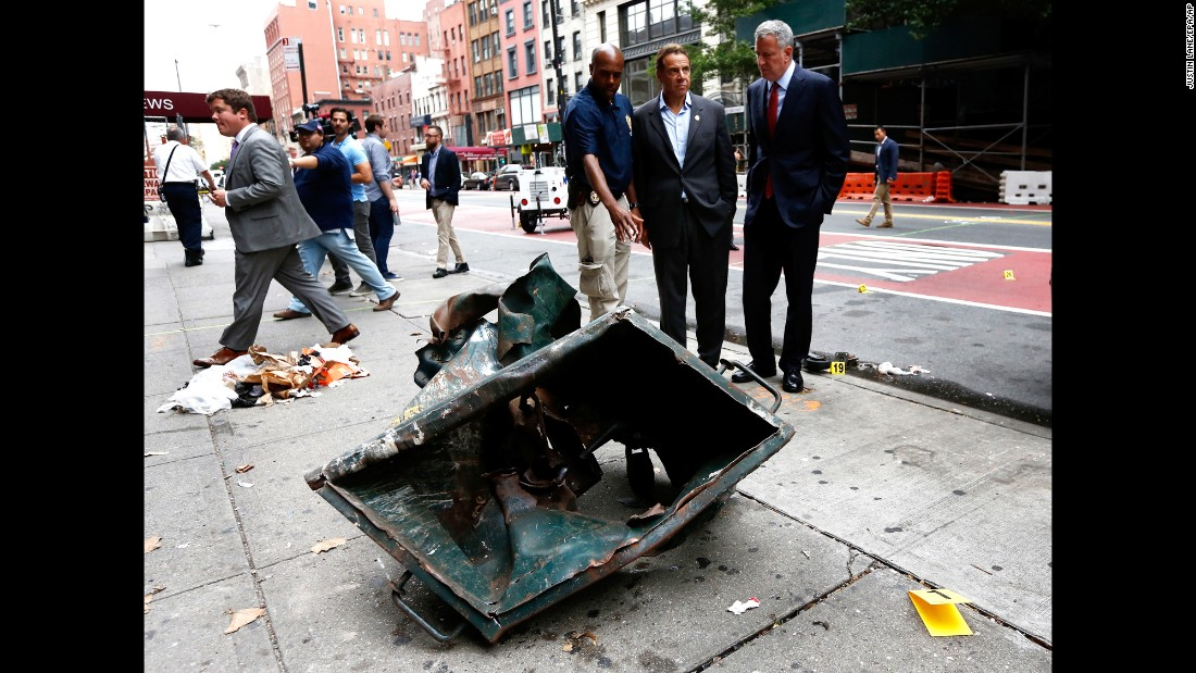 """New York Mayor Bill de Blasio, right, and New York Gov. Andrew Cuomo, second right, look over the mangled remains of a dumpster Sunday, September 18, in New York's Chelsea neighborhood. An explosion <a href=""""http://www.cnn.com/2016/09/17/us/gallery/ny-explosion-0917/index.html"""" target=""""_blank"""">injured 29 people there</a> the night before."""