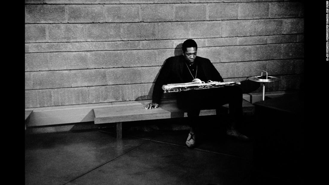 Saxophonist John Coltrane slumps on a bench backstage.