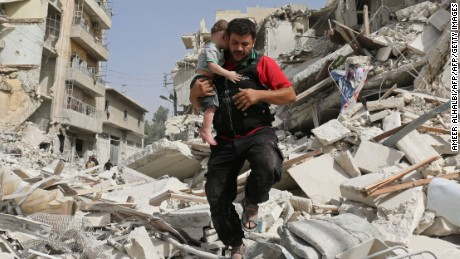 A Syrian man carries a baby after removing him from the rubble of a destroyed building following a reported air strike in the Qatarji neighbourhood of the northern city of Aleppo on September 21, 2016. Heavy bombardment pummelled Aleppo city and the wider province, key battlegrounds in Syria's conflict. The Syrian Observatory for Human Rights said dozens of raids hit the city's east overnight, as regime troops advanced on rebels in Aleppo's southwestern outskirts. / AFP / AMEER ALHALBI        (Photo credit should read AMEER ALHALBI/AFP/Getty Images)