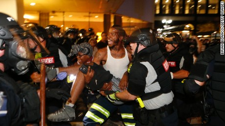 Police officers and protesters carry a man who was shot during a second night of protests in Charlotte, North Carolina, on Wednesday, September 21. The shooting victim, 26-year-old Justin Carr, later died.  Violent protests erupted in Charlotte following the death of Keith Lamont Scott, who was shot by police in an apartment complex parking lot. Charlotte-Mecklenburg Police Chief Kerr Putney said Scott exited his car with a gun and that he was shot after he wouldn't drop it. Scott's family said he was unarmed and sitting in his car reading a book.