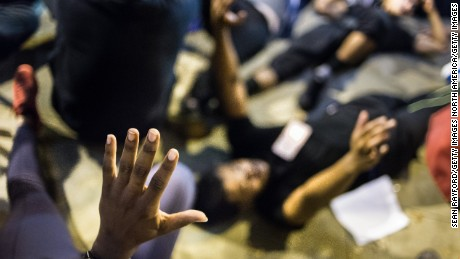 CHARLOTTE, NC - SEPTEMBER 22: Demonstrators protest in on the steps of the police station on September 22, 2016 in Charlotte, NC. Protests began on Tuesday night following the fatal shooting of 43-year-old Keith Lamont Scott at an apartment complex near UNC Charlotte. A state of emergency was declared overnight in Charlotte and a midnight curfew was imposed by mayor Jennifer Roberts, to be lifted at 6 a.m. (Photo by Sean Rayford/Getty Images)
