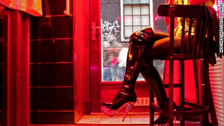 TO GO WITH AFP STORY BY ALIX RIJCKAERT A German prostitute, called Eve, waits for clients behind her window in the red light district of Amsterdam on December 8, 2008. Under a plan called Coalitions Project 2012, unveiled on December 6, 2008 by the city council, Amsterdam plans to halve the number of prostitution windows and cannabis-vending coffee shops in a revamp of its historic center aimed at curbing rising crime. Prostitution was legalized in the Netherlands in 2000             AFP PHOTO/ANOEK DE GROOT        (Photo credit should read ANOEK DE GROOT/AFP/Getty Images)