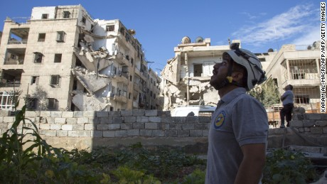 A Syrian rescuer looks towards the sky following an air strike in the rebel-held Ansari district of Aleppo on Thursday, September 23.