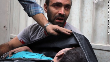 TOPSHOT - A Syrian man carries the body of his nephew following a reported airstrike on September 23, 2016, on the al-Muasalat area in the northern Syrian city of Aleppo.Missiles rained down on rebel-held areas of Syria's Aleppo, causing widespread destruction that overwhelmed rescue teams, as the army prepared a ground offensive to retake the city. / AFP / THAER MOHAMMED        (Photo credit should read THAER MOHAMMED/AFP/Getty Images)