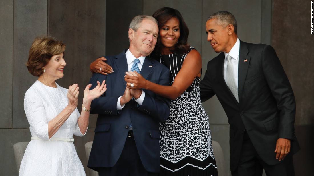 First lady Michelle Obama, center, hugs former President George W. Bush, as President Barack Obama and former first lady Laura Bush walk on stage at the dedication ceremony of the Smithsonian Museum of African American History and Culture on the National Mall in Washington on Saturday, Sept. 24.