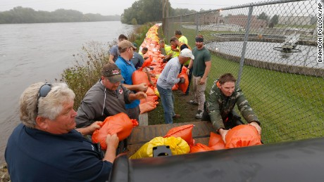 Volunteers and city workers place sandbags along the dike between the Cedar River and the water treatment plant in Cedar Falls, Iowa, Saturday, Sept.  24, 2016.   Authorities in several Iowa cities were mobilizing resources Friday to handle flooding from a rain-swollen river that has forced evacuations in several communities upstream, while a Wisconsin town was recovering from storms.  (Brandon Pollock/The Courier via AP)