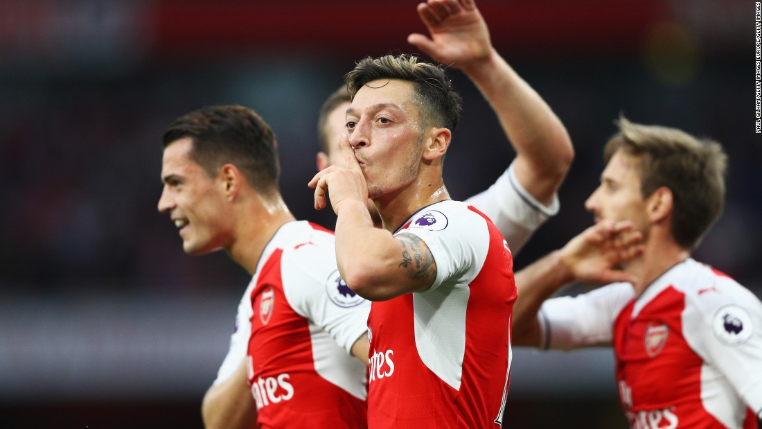 Mesut Ozil of Arsenal (C) celebrates scoring his side's third goal with teammates during the Premier League match between Arsenal and Chelsea at the Emirates Stadium.