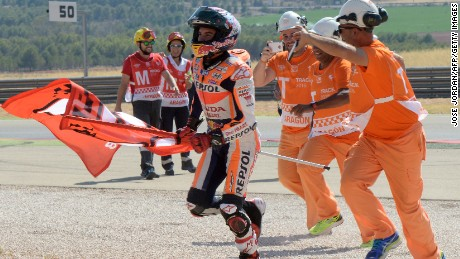 Marc Marquez celebrates his Aragon MotGP win with marshals at the Motorland track in Alcaniz.