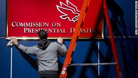 A worker cleans a sign for the Commission on Presidential Debates prior to the second presidential debate to be held at the David Mack Center at Hofstra University in Hempstead, New York, October 16, 2012.