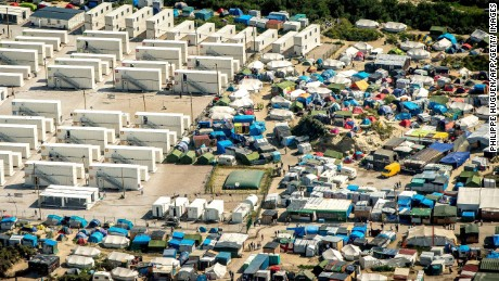"""This aerial view taken on August 16, 2016, in Calais, northern France shows the tents and the shipping containers housing migrants in the """"jungle"""" camp where over 9000 migrants live according to different NGOs. Some groups believe 9,000 people are now crammed into the Jungle, which is a largely makeshift camp although 1,750 residents are housed in more permanent accommodation created from shipping containers. / AFP / PHILIPPE HUGUEN        (Photo credit should read PHILIPPE HUGUEN/AFP/Getty Images)"""