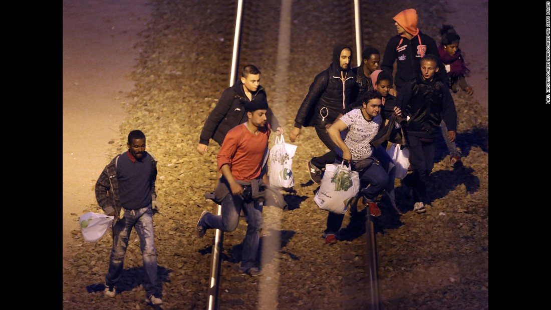 Migrants walk along the railway track leading to the Eurotunnel in Calais on August 10. Migrants attempt to enter the UK illegally by stowing away on trucks, ferries, cars or trains.