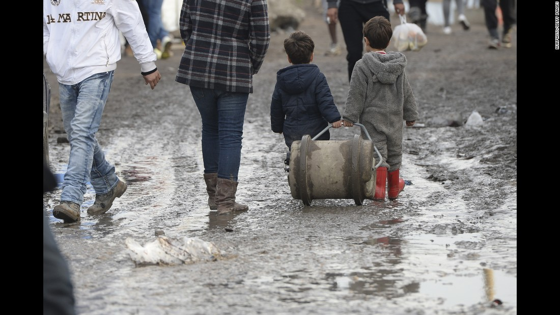"Two young boys walk in the mud inside ""The Jungle"" on December 19, 2015."