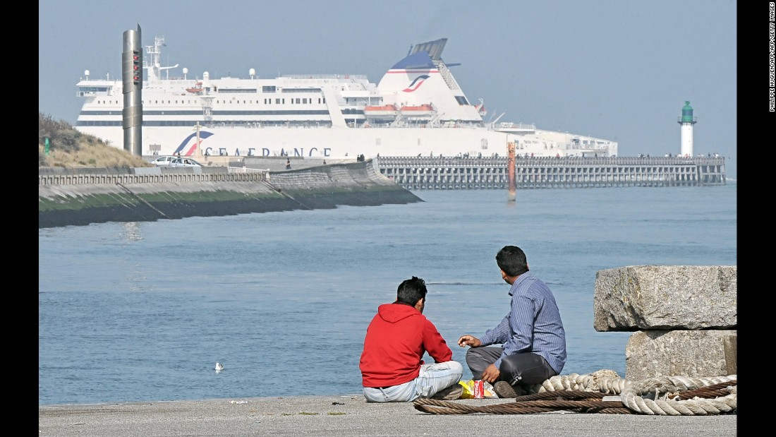 "Migrants from Afghanistan look at a ferry boat on the border of the Channel on September 19, in Calais, northern France. This was the same year former French immigration minister, Eric Besson, announced the Government would close the camp. However, in 2016, thousands still occupy ""The Jungle."""