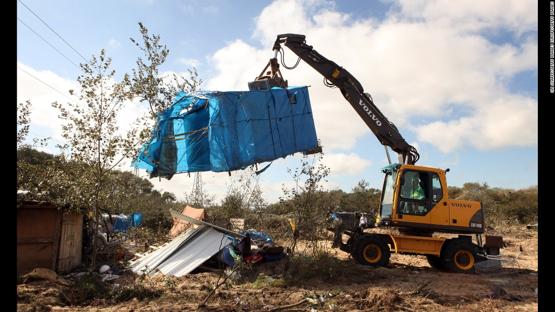 A digger lifts a migrant's makeshift tent during one of the destruction operations at the migrant camp on September 22. French police removed around 300 migrants who were taken to centers in Calais where they could apply for voluntary assisted repatriation or asylum.