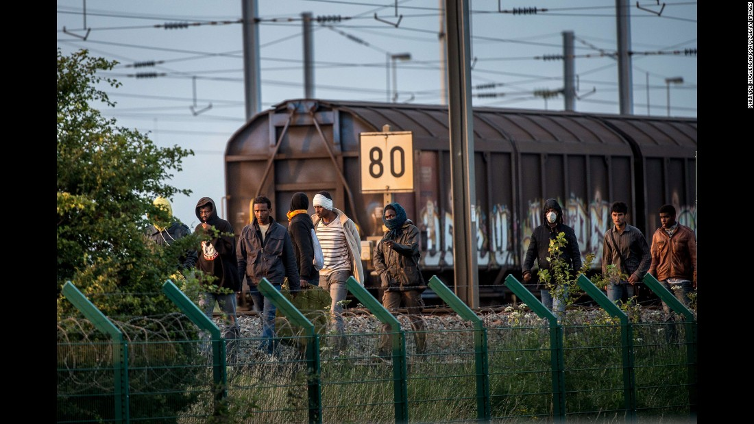 Several migrants successfully cross the Eurotunnel terminal on July 28, and walk on the side of the railroad as they try to reach a shuttle to the UK.